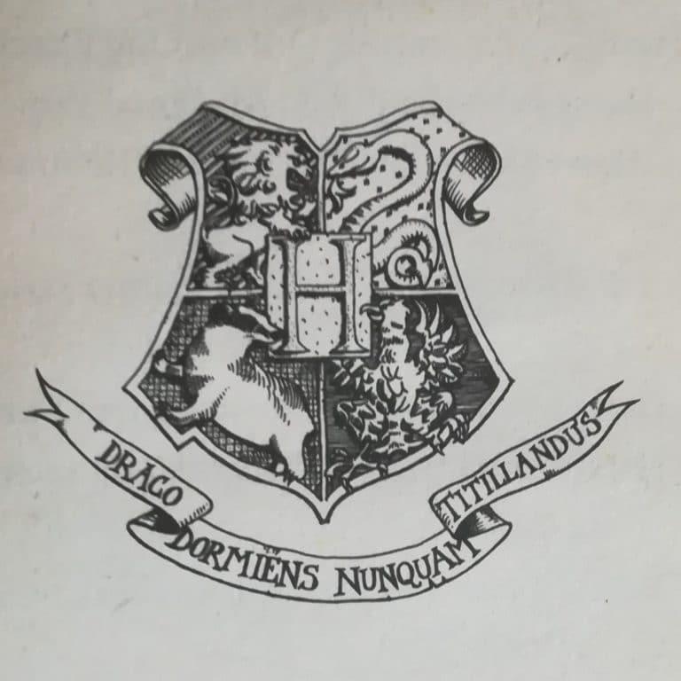 Blason de Poudlard sur lequel on peut lire en latin : Draco Dormiens Nunquam Titilandus.